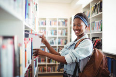 Colegiala que selecciona el libro de estante de librería en biblioteca en la escuela Fotos de archivo