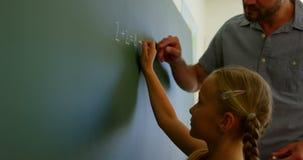 Colegiala que soluciona la ecuación matemática en la pizarra en la sala de clase 4k metrajes