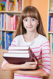 Colegiala que sostiene el libro en la biblioteca Imagen de archivo libre de regalías