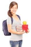Colegiala que sostiene una pila de libros y de una manzana Foto de archivo