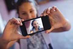 Colegiala que toma el selfie en el teléfono móvil Imagen de archivo