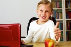 Colegiala que trabaja en un ordenador portátil Imagenes de archivo