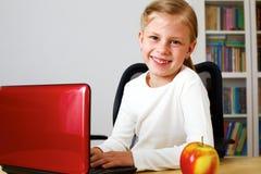 Colegiala que trabaja en un ordenador portátil Fotos de archivo