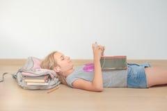 Colegiala que usa el teléfono móvil en sala de clase Imágenes de archivo libres de regalías