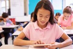 Colegiala que usa la tableta en clase de la escuela primaria Imágenes de archivo libres de regalías