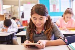 Colegiala que usa la tableta en clase de la escuela primaria Imagen de archivo