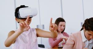 Colegiala que usa las auriculares de la realidad virtual en sala de clase metrajes