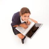 Colegiala que usa una computadora portátil Imagen de archivo
