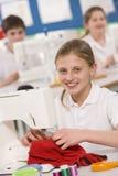 Colegiala que usa una máquina de coser en clase de costura Imagenes de archivo