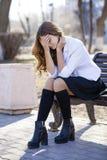 Colegiala rubia hermosa joven que se sienta en un banco Foto de archivo libre de regalías