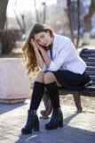 Colegiala rubia hermosa joven que se sienta en un banco Fotos de archivo