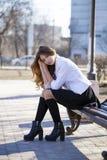 Colegiala rubia hermosa joven que se sienta en un banco Imagen de archivo libre de regalías