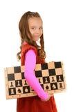 Colegiala sonriente con el tablero de ajedrez Imagen de archivo libre de regalías