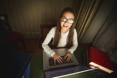 Colegiala sonriente en las lentes que trabajan en el ordenador en el ro oscuro Imagen de archivo libre de regalías