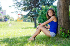Colegiala sonriente feliz que se sienta en el árbol en parque el día de verano Imagen de archivo