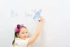 Colegiala sonriente que aprende escribir la letra B Imagen de archivo libre de regalías