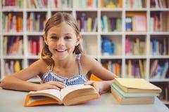 Colegiala sonriente que lee un libro en biblioteca Fotografía de archivo libre de regalías