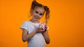 Colegiala sonriente que lleva a cabo el piggybank y que mira a la cámara, actividades bancarias para los niños fotos de archivo libres de regalías