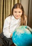 Colegiala sonriente que presenta con el globo de la tierra en el gabinete Foto de archivo