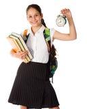 Colegiala sonriente que se coloca con el libro y el despertador Fotos de archivo libres de regalías
