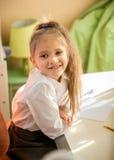 Colegiala sonriente que se sienta en el escritorio en dormitorio Imagen de archivo libre de regalías