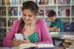 Colegiala sonriente que usa el teléfono móvil en biblioteca Foto de archivo libre de regalías