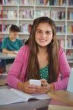 Colegiala sonriente que usa el teléfono móvil en biblioteca en la escuela Foto de archivo