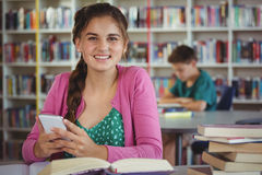Colegiala sonriente que usa el teléfono móvil en biblioteca en la escuela Fotografía de archivo libre de regalías