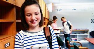 Colegiala sonriente que usa el teléfono móvil en sitio de clase almacen de video