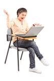 Colegiala sorprendida que mira un ordenador portátil Fotos de archivo libres de regalías