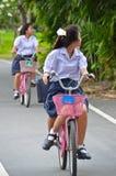 Colegiala tailandesa que monta una bicicleta Imágenes de archivo libres de regalías