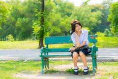 Colegiala tailandesa tímida que se sienta en un banco Foto de archivo libre de regalías