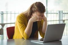 Colegiala triste con el ordenador portátil en la tabla en biblioteca Fotografía de archivo libre de regalías