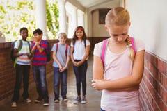 Colegiala triste con los amigos en fondo en el pasillo de la escuela Imagen de archivo