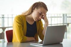 Colegiala triste que mira el ordenador portátil en biblioteca Imágenes de archivo libres de regalías