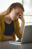 Colegiala triste que mira el ordenador portátil en biblioteca Foto de archivo