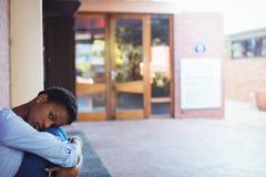 Colegiala triste que se sienta en campus de la escuela Imagenes de archivo