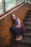 Colegiala triste que se sienta solamente en escalera Fotografía de archivo libre de regalías