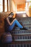 Colegiala triste que se sienta solamente en escalera Fotos de archivo