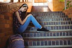 Colegiala triste que se sienta solamente en escalera Imagenes de archivo