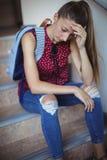 Colegiala triste que se sienta solamente en escalera Foto de archivo libre de regalías