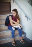 Colegiala triste que se sienta solamente en escalera Fotografía de archivo