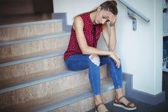 Colegiala triste que se sienta solamente en escalera Foto de archivo