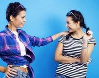 Colegialas adolescentes de los mejores amigos junto que se divierten, presentación emocional en el fondo azul, sonrisa feliz de l Imagen de archivo