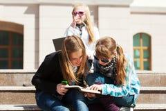 Colegialas adolescentes en los pasos del campus Imágenes de archivo libres de regalías