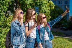 Colegialas de las muchachas en verano en parque Él toma imágenes de sí mismo en el teléfono Actitud sonriente feliz en cámara En  Foto de archivo
