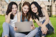 Colegialas emocionadas con el ordenador portátil en el patio de escuela Fotografía de archivo