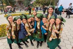 Colegialas felices en los vestidos georgianos coloridos tradicionales que se divierten al aire libre durante el día od la ciudad Imagen de archivo libre de regalías