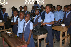 Colegialas jovenes y muchachos haitianos que cantan en sala de clase en la escuela Imágenes de archivo libres de regalías