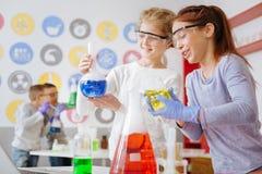 Colegialas optimistas que comprueban para saber si hay la reacción química deseada en frasco Foto de archivo libre de regalías